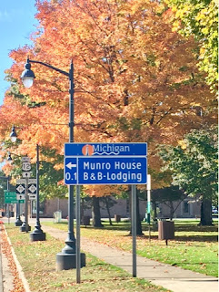 Blue Michigan road sign along highway 12 during peak fall color season with green yellow orange and red leaves