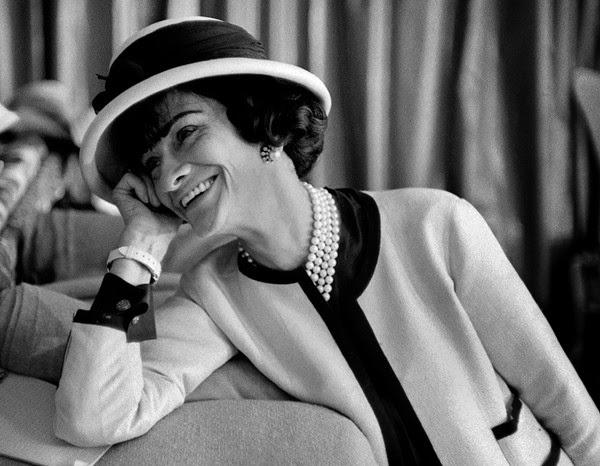 Coco Chanel 穿着經典的 tweed 短外套,斜紋軟呢是她在蘇格蘭時發現的。
