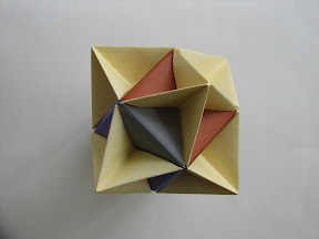"Cube from Sonobe units with Alpha. Instructions in Tomoko Fuse's ""Multidimensional Transformations: Unit Origami"", page 74."