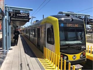 Et gult tog som står langs en perrong.
