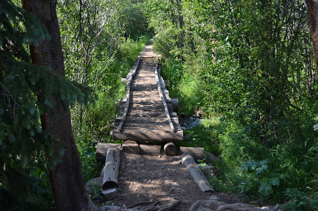 a long bridge of built with round logs for the planking