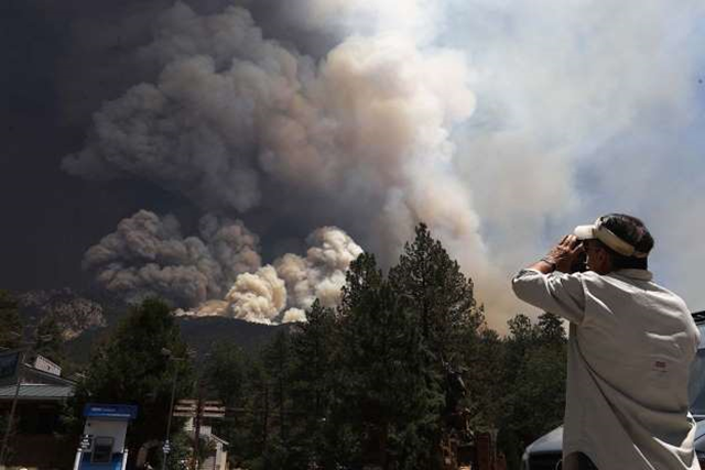 The Cranston fire burns as a man takes photos on 26 July 2018, near Idyllwild, California. Fire crews are battling the 4,700-acre fire in the midst of a heat wave. Photo: Mario Tama / Getty