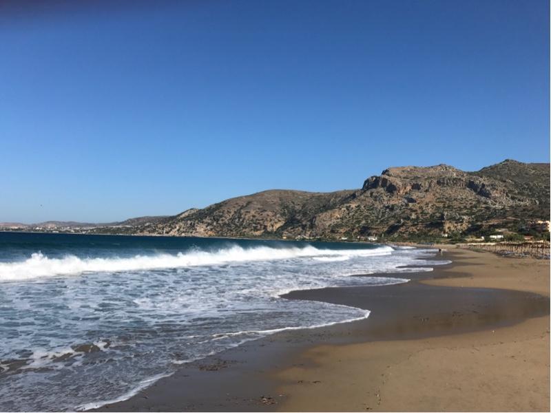 Sandstrand med skummende bølger som slår mot land.