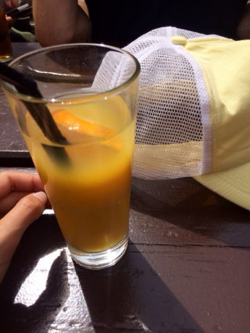 photo of orange juice on a table in the sun with a yellow cap