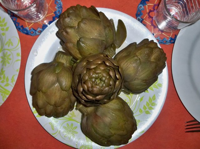 5 artichokes atfully placed on a dish