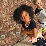Two children looking up at a camera with a hula hoop round them and wearing George clothing