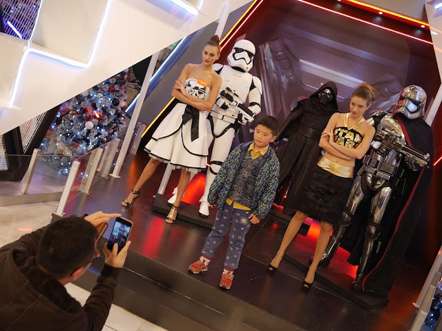 boy posing for photo with femal Star Wars models and life size statues at the IAPM shopping center in Shanghai