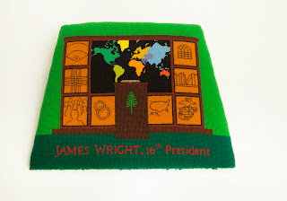 "A needlepoint seat cover reading ""James Wright, 16th president"" and showing a podium world map, among other images."