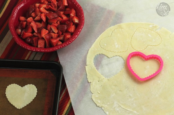 Cutting out crust heart shapes for strawberry pie
