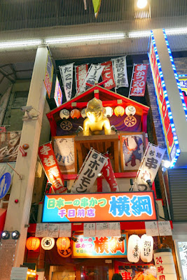 Billiken is the defining symbol of the area around Tsutenkaku but can be found in various places in Osaka and is the god of 'things as they ought to be'. Rubbing his feet brings luck, and oddly he is a charm character imported from St Louis but adopted into Japanese culture
