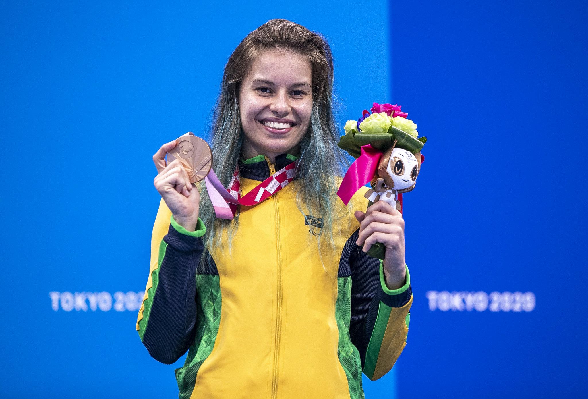 Beatriz sorri para a câmera, vestindo o agasalho da delegação brasileira e segurando sua medalha e um buquê de flores
