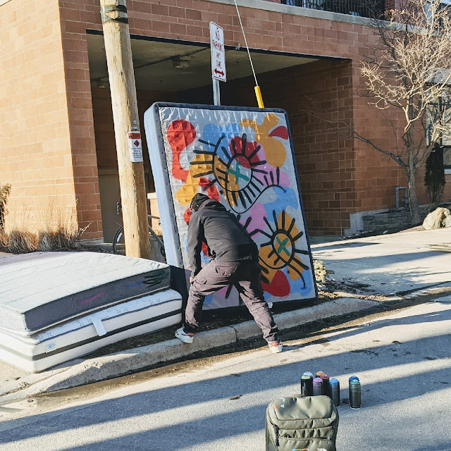 picture of a person spray painting a mattress on a street