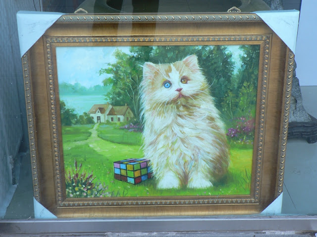 painting in Tianjin, China, of a Rubiks Cube and a cat with differently colored eyes in front of a pathway to a rural house
