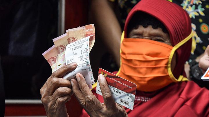 Warga Lanjut usia (Lansia) dari Keluarga Penerima Manfaat (KPM) menunjukkan uang bantuan Program Keluarga Harapan (PKH) di Bekasi, Jawa Barat, Kamis, 7 Januari 2021. Pemerintah melalui APBN 2021 menyiapkan anggaran sebesar Rp110 triliun untuk tiga jenis bantuan yakni Program Keluarga Harapan (PKH), Program Sembako dan Bantuan Sosial Tunai (BST). ANTARA FOTO/ Fakhri Hermansyah
