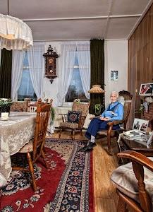 Mvr Gijs Hoogenhoud Coers. Leeftijd 88 jaar. Woont sinds 1954 op deze boerderij aan de Ronde Hoep in de buurt van Ouderkerk a/d Amstel. Zij kwam daar bij haar man wonen en nam deel aan het boeren bedrijf. Daarvoor had ze een kaaswinkel in de Kinkerbuurt te Amsterdam.Ze heeft een tijdje de kaaswinkel aan gehouden voordat ze volledig in het boerenbedrijf stapte. Dat betekende s'ochtends vroeg de koeien melken en dan daarna op de fiets naar de winkel in Amsterdam. Op de boerderij hielden ze 40 melkoeien, 10 stuks jongvee(kalfjes en pinken) en paarden.Het boerenbedrijf is al lang geleden overgenomen door haar dochter. Haar man is een aantal jaar geleden overleden. Ze heeft nog veel veel broer en zussen in Canada wonen die daar na de oorlog naartoe zijn geemigreerd om een boeren bedrijf te beginnen. Ze is vast besloten nog lange tijd op de boerderij te blijven wonen omdat ze het daar erg naar haar zin heeft. Ruimte, frisse lucht etc. Heeft genoeg aanloop en de telefoon is soms goed genoeg vind ze. Lezen en tuinieren is ook een fijne bezigheid.