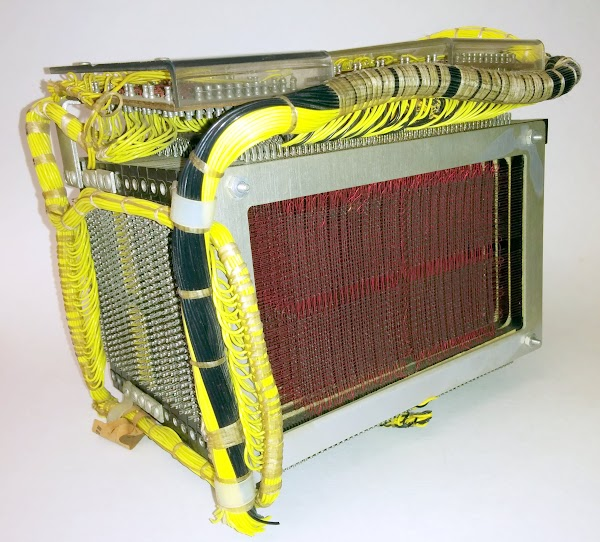 The core memory module from the IBM 1401 mainframe. The cores in one of the planes are visible, strung along red wires. At the top, two matrix decoder boards generate the 50 X select lines and 80 Y select lines, addressing one of 4000 storage locations. The X select lines are connected to the core planes by the yellow wires on the left side of the core module, while the Y select lines are connected on top.