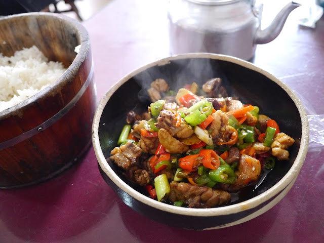 spicy chicken dish next to a wooden bucket of rice in Changsha, Hunan