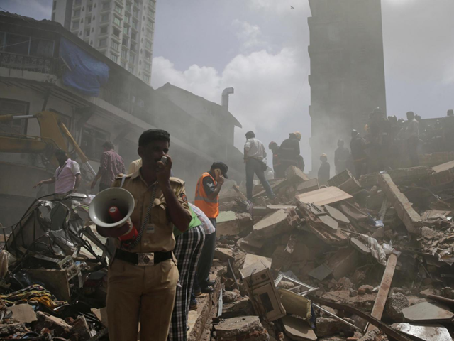 A policeman makes an announcement on a loudspeaker at the site of the building collapse in Mumbai, India, 31 August 2017. Photo: Rafiq Maqbool / AP