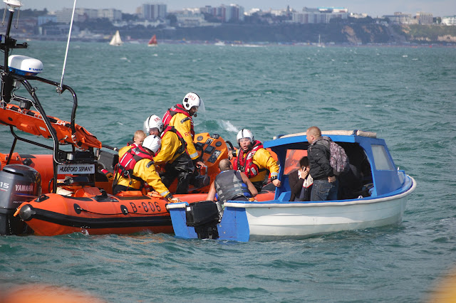 30 August 2012 - Mudeford lifeboat alongside an open boat and taking off four of the people onboard that had been struggling with the tide and wind conditions in Poole Bay on the first day of the Bournemouth Air Show. Photo: RNLI Poole/Dave Riley