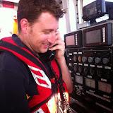 Crew member Alex Evans on radio duties on the ALB. 13 June 2014.  Photo credit: Dave Riley, Poole RNLI
