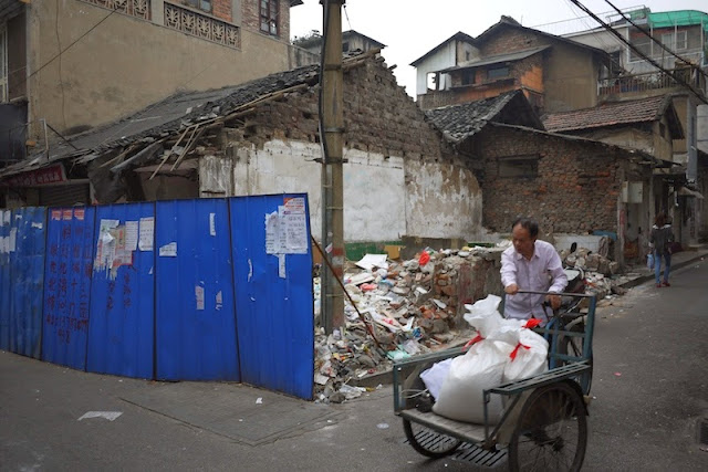 man with tricycle cart next to a partially demolished building at Beizheng Street in Changsha, China