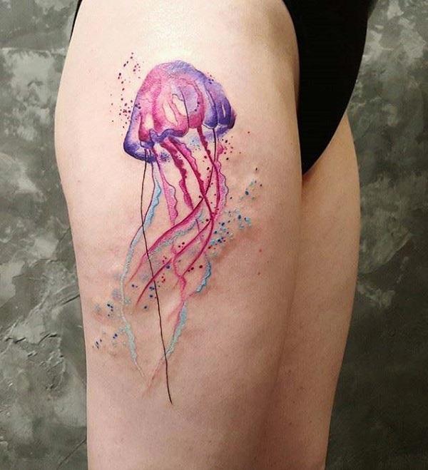 Bela medusa tatuagem na coxa. As cores são muito bonitas e se complementam. Você pode ver como serena, a água-viva parece tão suavemente flutua em torno. As bolhas coloridas também circundantes a água-viva olhar muito misterioso e místico.