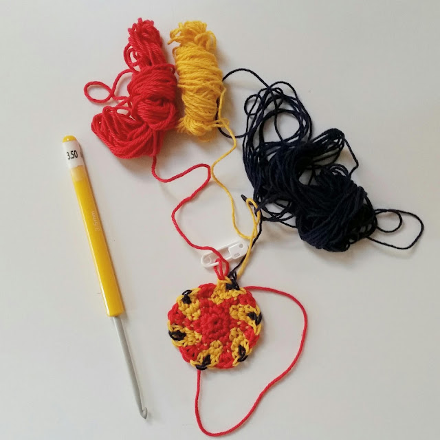 A crocheted circle with a red centre and red arms gently spiralling outwards interspersed with yellow V-shapes which have dark blue between the stems of the Vs.