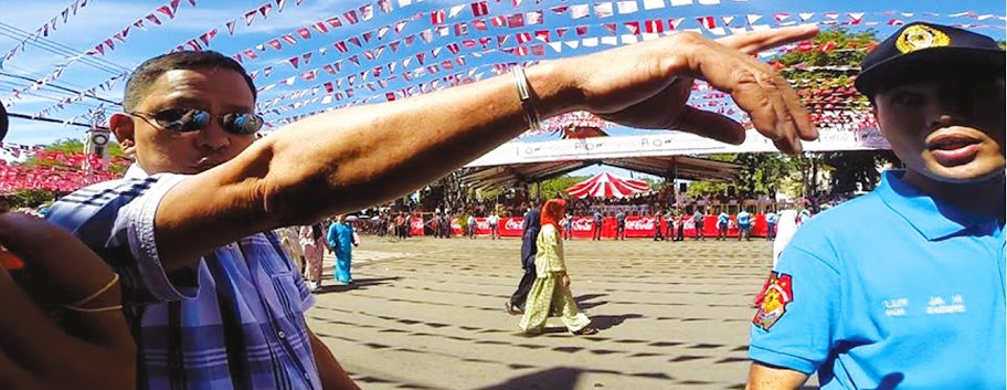 Marshal shooing off photographers during Kadayawan in Davao City