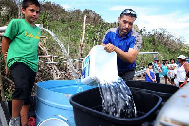 Robert Rodriguez (left) and Josue Mendez collect water from a mountain creek on a road to the town of Utuado, Puerto Rico. Photo: Pedro Portal / Miami Herald