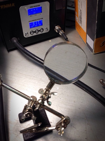 A helping hands magnifier in front of a temperature controller SMD rework soldering station.