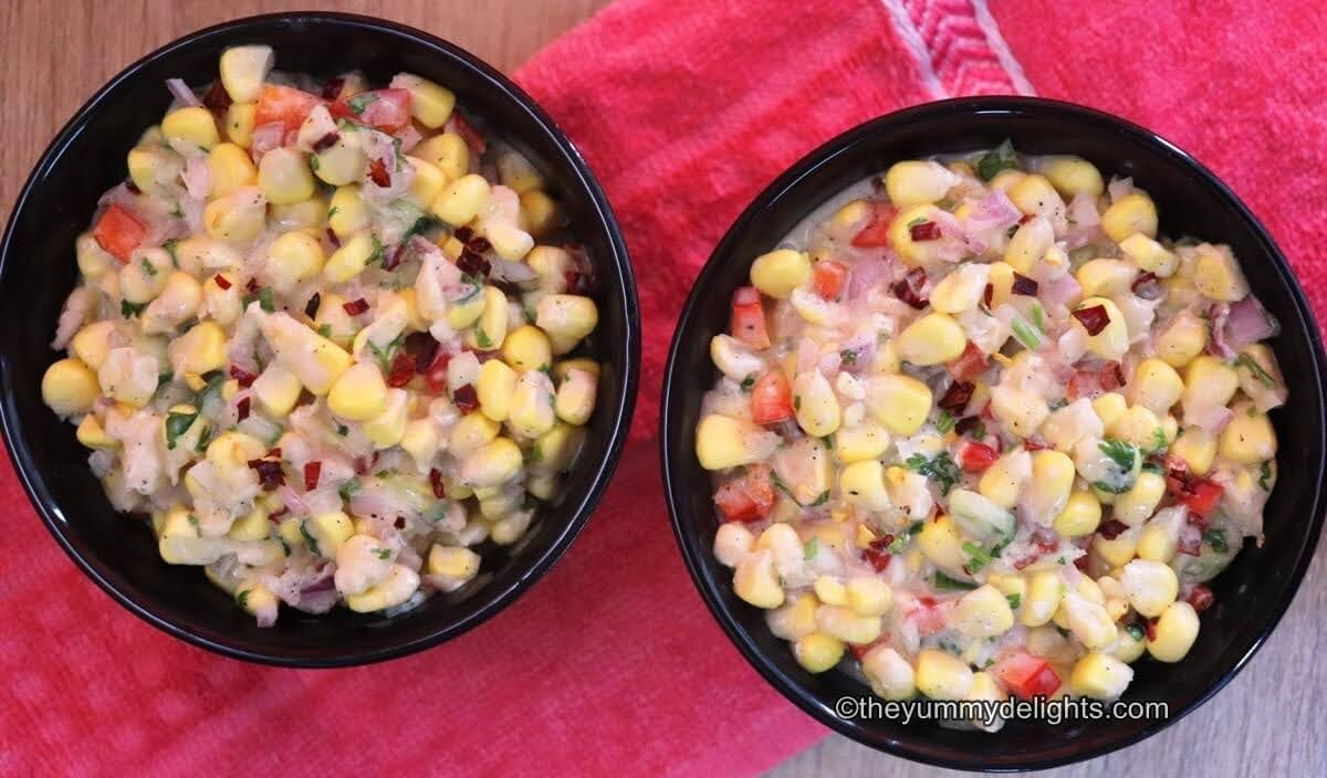 corn salad with creamy greek yogurt and mayo dressing. Served in two black bowls placed over a red cloth.
