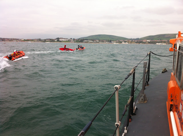 20 May 2012: Swanage inshore lifeboat returning to a capsized dinghy being towed by a sailing club safety boat in Swanage Bay after the lifeboat crew had taken a gentleman ashore who had been in the water. Photo: RNLI/Poole Dave Riley