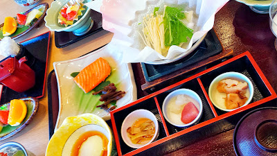 Breakfast at Wakakusa no Yado Maruei - a tofu and mushroom broth, salmon, fruit, some sort of custard thing in the yellow bowl and a trio of three little bites in a lacquered tray