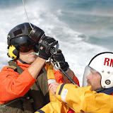 Crew member preparing to be lifted during a helicopter exercise with Portland Coastguard