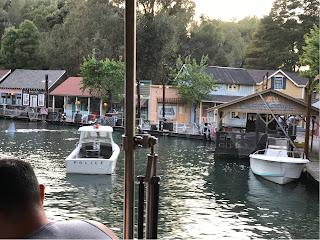 En «havneby» med trehus og båter på vannet. En haifinne sees til venstre på bildet.