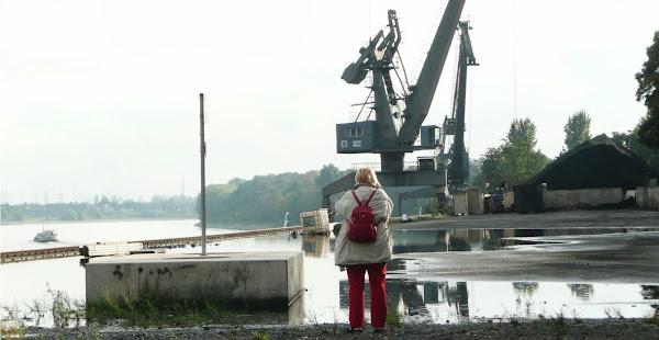 Hafen: Besucherin blickt auf Rhein und Kran.