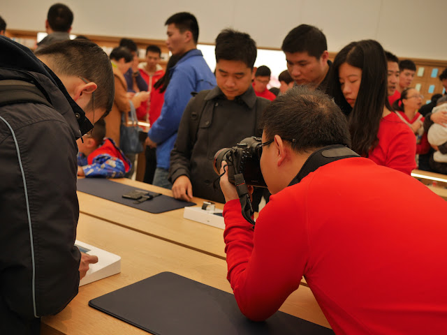Apple employee taking a photograph with a Canon camera at the SM Lifestyle Center Apple Store in Xiamen, China