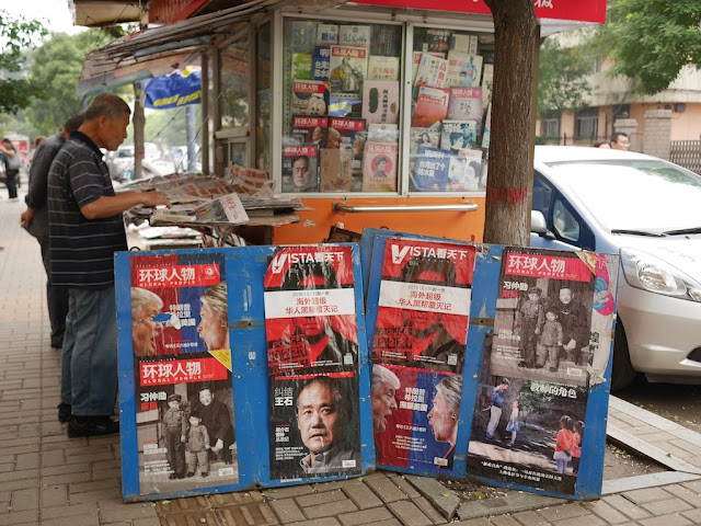 newsstand in Taiyuan displaying covers of various magazines including one featuring Donald Trump and Hillary Clinton