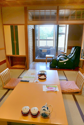 At our ryokan Wakakusa no Yado Maruei, this is the main room after removing our shoes in the foyer and walking through our sliding door screen. You can see a little closet with onsen supplies (robes, a plastic bag for carrying things to the onsen rooms) on the left, and our private onsen with a view of a small rock garden and Mount Fuji to the back behind the glass, after the massage chair