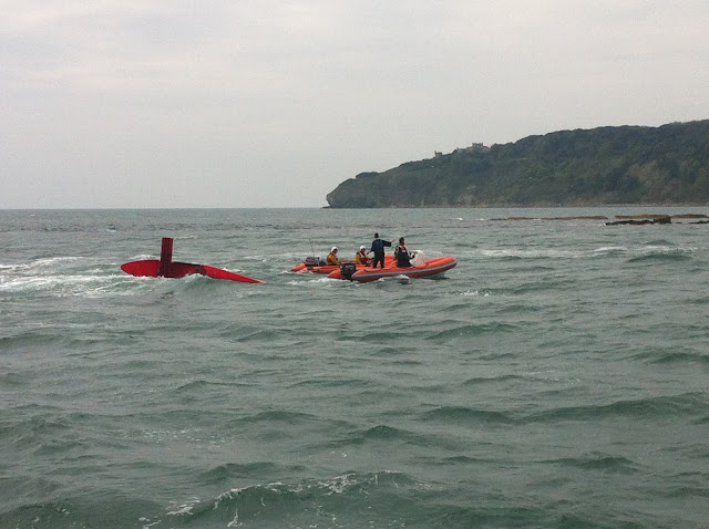 20 May 2012: Swanage inshore lifeboat alongside a capsized dinghy and sailing club safety boat in Swanage Bay after they had been struggling with the tide and wind on Peveril Ledge. Photo: RNLI/Poole Dave Riley