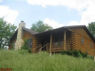 Photo of a log cabin home with a stone fireplace and a lot of overgrown grass.