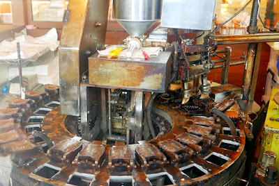 Automated Ningyo Yaki Machine. On the right side, you can see two pipes that brush the inside of the mold, and then the machine will squeeze the dough into the molds, On the other side the bean is then added, and more dough on top then the molds continue to circle, cooking it on one side until it is flipped by that lever you see on the right to cook on the other side! It ticks more counterclockwise until it gets to the lever on the right which will open and dump out the ningyo yaki