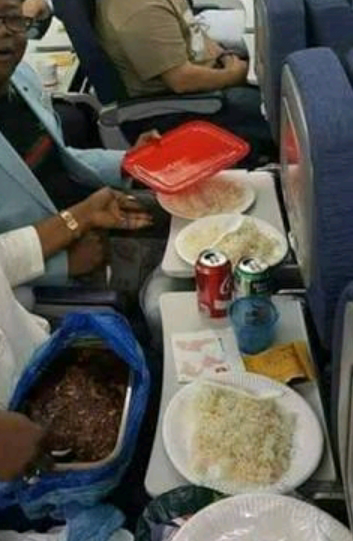 A Nigerian man eating rice and stew with his wife in an aeroplane