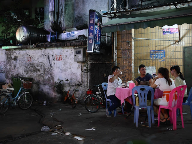 four people eating dinner at a table outside in an alley