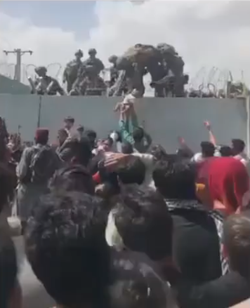 Afghan mum hands baby over barbed wire to American soldier for evacuation (video)