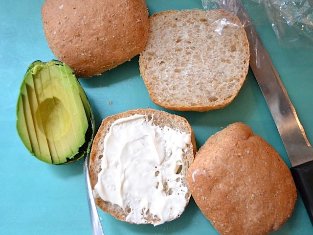 hamburger buns with mayo spread on one side and an avocado sliced and ready to put on