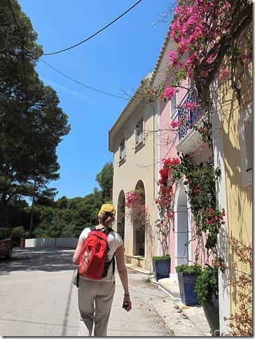 Woman walking along street in Assos, Greece photo by Sue Wellington