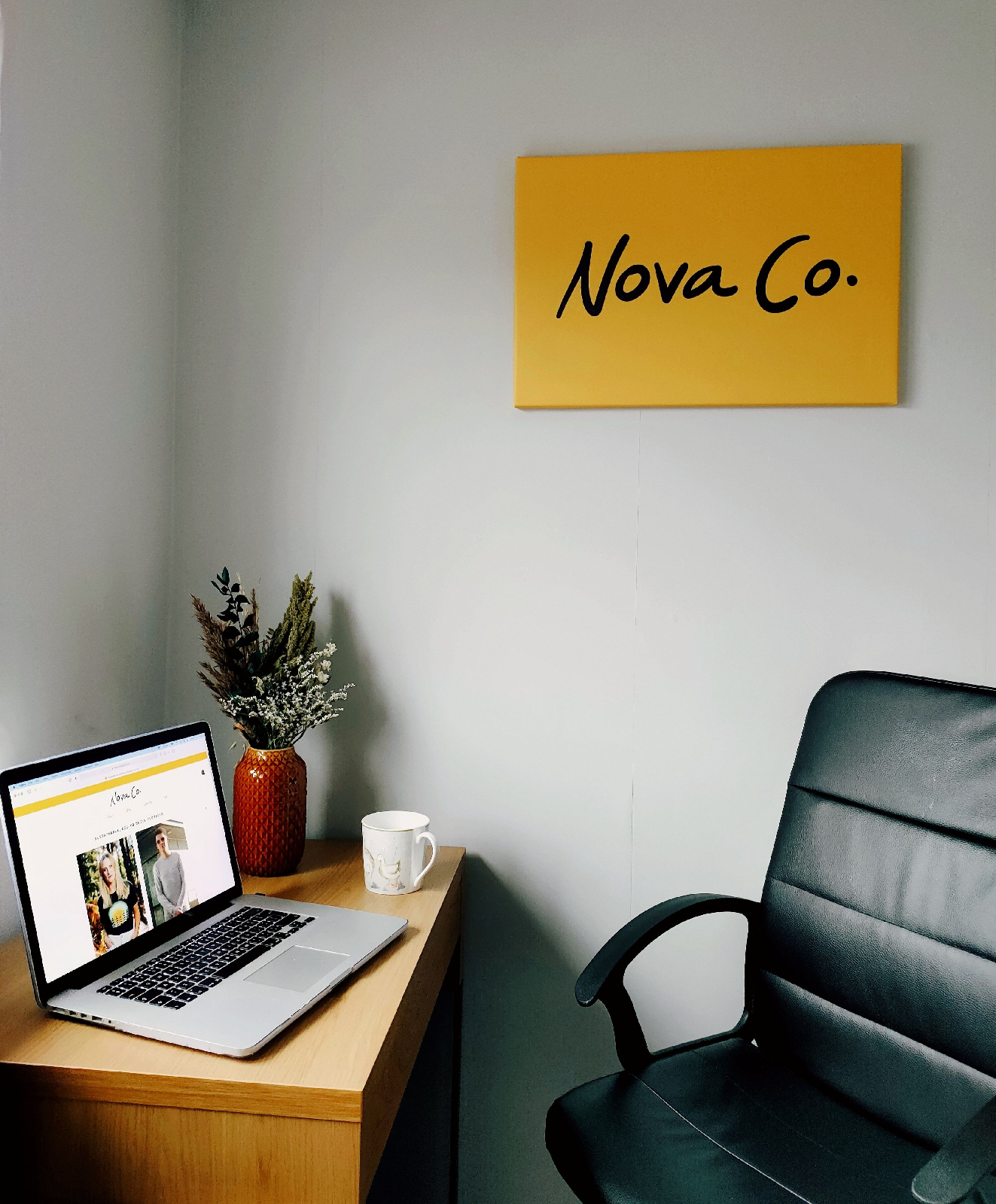 a desk and a chair with a canvas on the wall; there is a laptop and some flowers on the desk