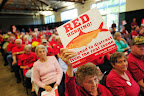 A woman holds a red herring sign as a proponent of the Millennium Bulk Terminal speaks of the benefit of the project.