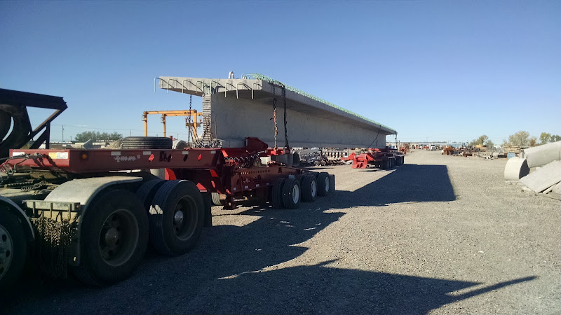 oversized cement bridge beam loaded on flatbed trailer and dolly